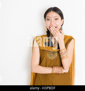Portrait of shocked mixed race Indian Chinese girl in traditional punjabi dress covering her mouth, surprised emotion, - Stock Photo