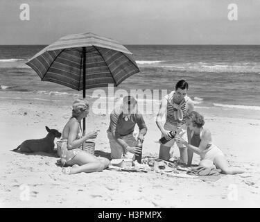 1930 1930s TWO COUPLES TWO MEN TWO WOMEN HAVING PICNIC ON BEACH BY OCEAN WITH TERRIER DOG UNDER STRIPED UMBRELLA - Stock Photo