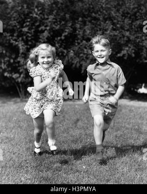 1930s 1940s SMILING BOY AND GIRL RUNNING IN SUMMER BACKYARD GRASS LOOKING AT CAMERA - Stock Photo