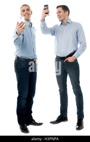 Two young men using their phone - Stock Photo