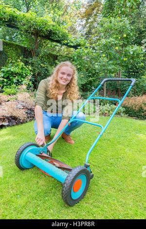 Young caucasian woman reparing lawn mower on green grass - Stock Photo