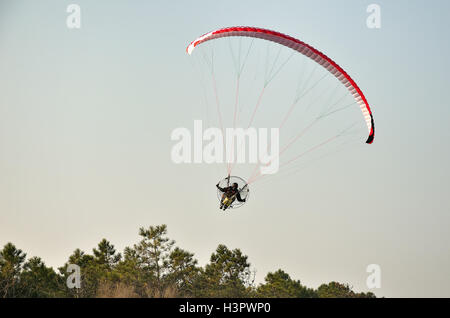 Paraglider in flight in blue sky - Stock Photo