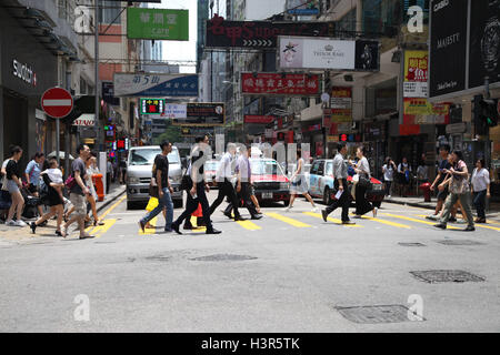 People crossing a busy road in Central Hong Kong - Stock Photo