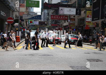 Chinese people crossing road in central district, Hong Kong island, China, Asia. - Stock Photo