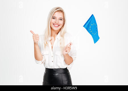 Cheerful beautiful young businesswoman holding flag of European union and showing thumbs up over white background - Stock Photo