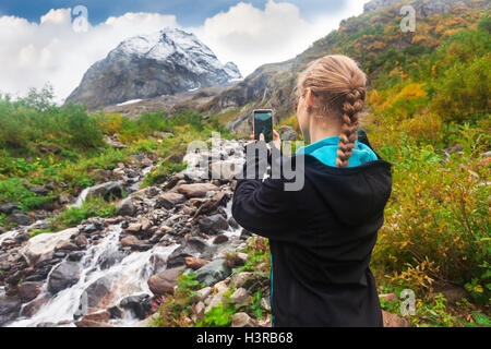 woman taking a photo of mountin on smartphone - Stock Photo