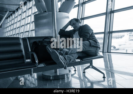 Man sleeping in the airport - Stock Photo