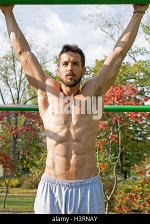 Young Athlete Working Out in an Outdoor Gym. Street Workout Exercises. - Stock Photo
