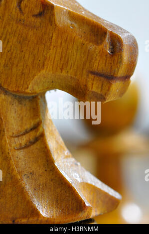 Chess pieces on the chessboard, knight in the foreground, pawn, queen and knight on the background in a white background - Stock Photo