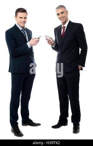 Smiling businessmen using cellphone - Stock Photo