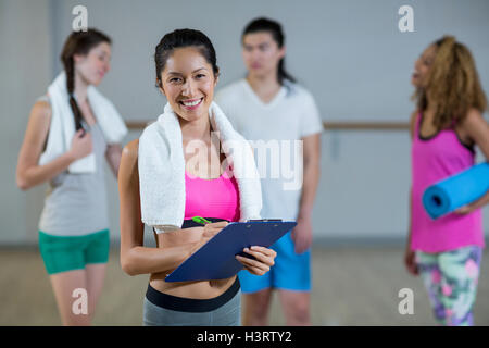 Portrait of female trainer holding clipboard - Stock Photo