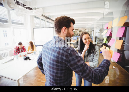 Businesswoman looking coworker writing on sticky notes - Stock Photo