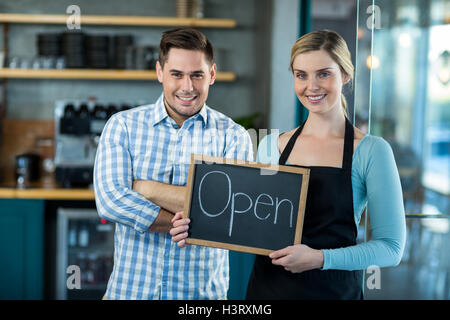 Waitress and man standing with open sign on slate in cafe - Stock Photo