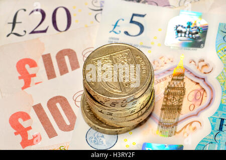 British money - pound coins on notes, including new (2016) polymer £5 - Stock Photo