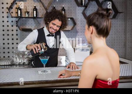 Waiter pouring cocktail in womans glass at bar counter - Stock Photo