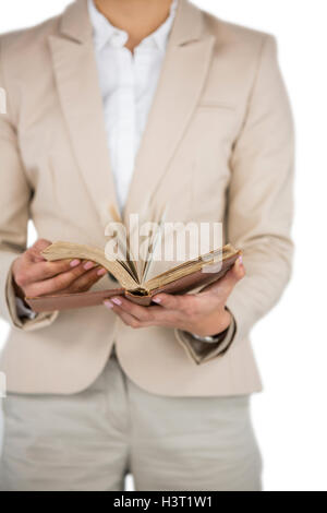 Mid section of Businesswoman flips through the pages of a book - Stock Photo