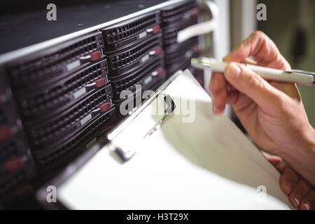 Close-up of technician maintaining record of rack mounted server on clipboard - Stock Photo