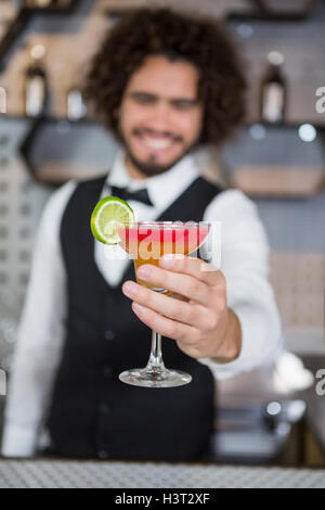 Bartender holding glass of cocktail in bar counter - Stock Photo