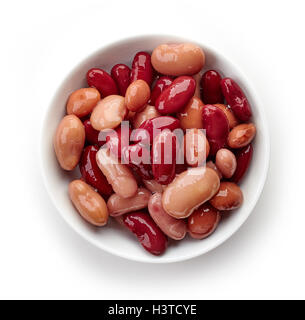Various types of canned beans in bowl isolated on white background, top view - Stock Photo