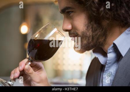 Businessman having glass of red wine - Stock Photo