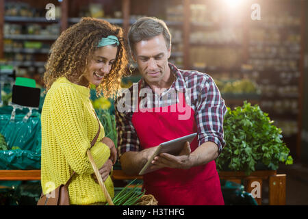 Woman looking at digital tablet used by the staff - Stock Photo