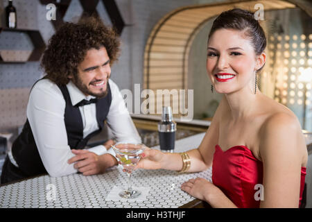 Portrait of beautiful woman standing at bar counter - Stock Photo