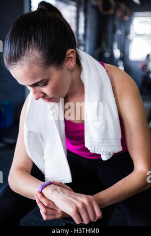 Female athlete checking time in gym - Stock Photo