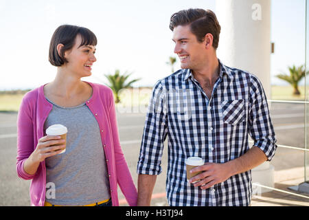Couple with coffee cups walking together - Stock Photo