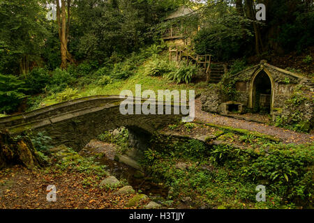 The bridge crossing the Cyflymen stream leading to the font and summerhouse in the gardens at Plas Newydd Llangollen - Stock Photo