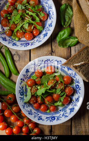 Salad of arugula and cherry tomatoes with basil pesto, jung peas and herbs inside - Stock Photo