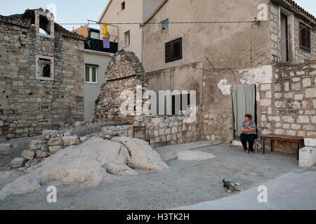 An elderly woman sitting in front of her house at the Adriatic coast. Kastela, Split-Dalmatia County, Croatia, Europe. - Stock Photo