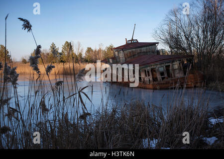 Abandoned shipwreck on the banks of the Pripyat River after the Chernobyl disaster. Pripyat, Chernobyl Exclusion - Stock Photo