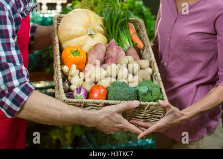 Male staff assisting a woman with grocery shopping - Stock Photo