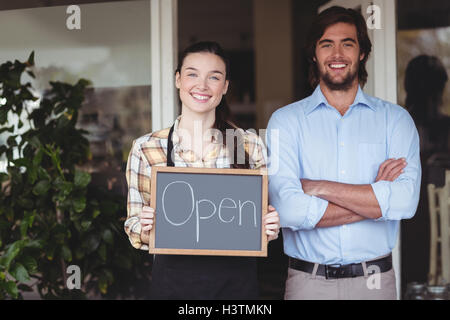 Man and waitress holding chalkboard with open sign - Stock Photo