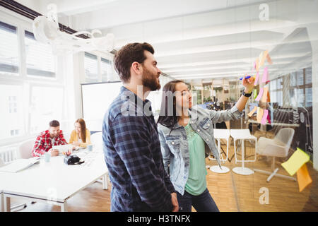 Smiling business people looking at multi colored sticky notes on glass - Stock Photo