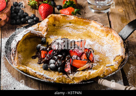 Dutch Baby Pancakes with berries and chocolate, baked in oven on iron pan, best pancakes ever!!! - Stock Photo
