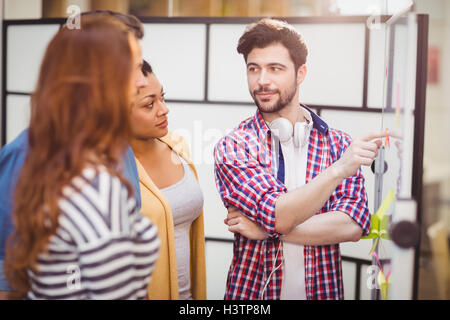 Confident executive interacting in meeting room at creative office - Stock Photo