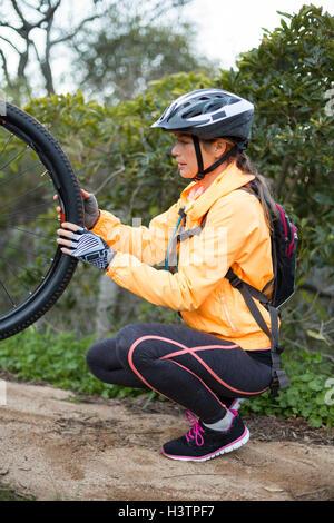 Female biker repairing mountain bike - Stock Photo