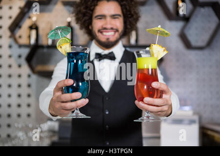 Bartender holding two glass of cocktail in bar counter - Stock Photo