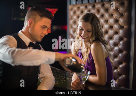 Waiter pouring a cocktail in woman glass at bar counter - Stock Photo