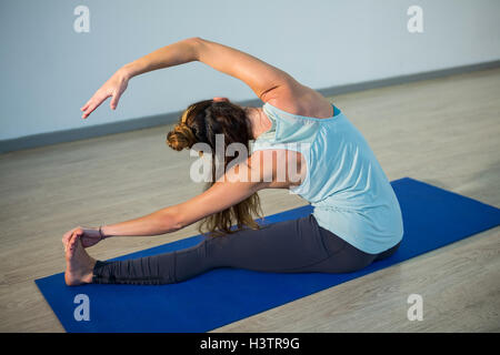 Woman performing head of the knee pose on exercise mat - Stock Photo