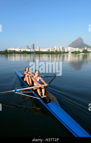 Two young women participating in early morning rowing training in the Lagoa Rodrigo de Freitas Lagoon, with Rio - Stock Photo