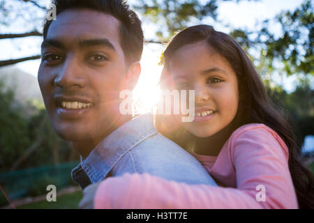 Father giving piggyback ride to his daughter - Stock Photo