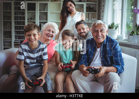 Family watching the kids playing video game - Stock Photo