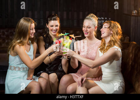 Female friends toasting glasses of cocktail in bar - Stock Photo