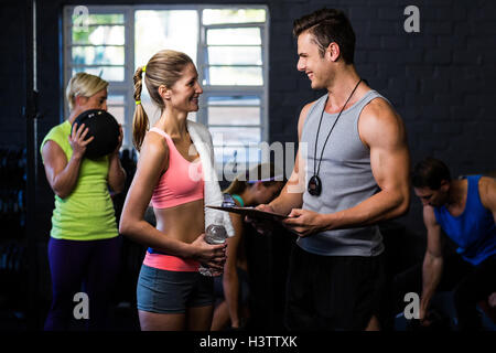 Woman talking with trainer in gym - Stock Photo