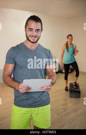Portrait of smiling fitness trainer holding clipboard - Stock Photo