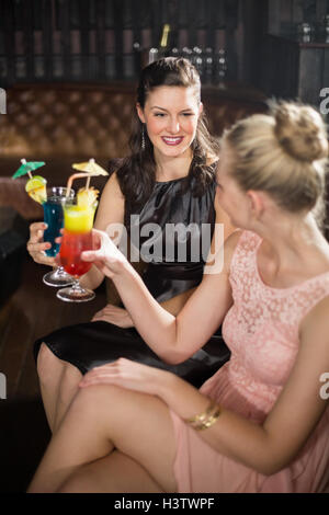 Female friends toasting glasses of cocktail - Stock Photo