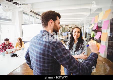 Female photo editor standing near male coworker - Stock Photo