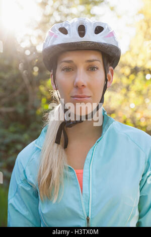 Portrait of female mountain biker in the forest - Stock Photo